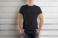 Ung man i en svart T-tröja och jeans på vita trälodisar royaltyfri foto
