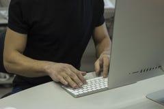 Ung man i en svart T-tröja som arbetar med datoren, man& x27; s-händer på tangentborddatoren Arkivbild