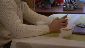 Ung man i en vit tr?ja med en smartphone som dricker kaffe p? ett kaf?, vid f?nstret 4K stock video