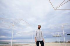 Ung man i ett vitt T-tröjaanseende på kusten mot bakgrunden av järnledstängerna arkivfoto