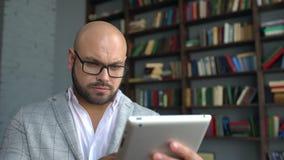 Ung man i exponeringsglas genom att använda minnestavlaPC som hemma surfar internet, ung man i exponeringsglasarbete i minnestavl arkivfilmer