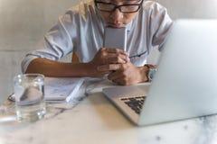 Ung man i exponeringsglas som framme stänger ögon av bärbara datorn arkivbild