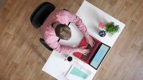 Ung man i exponeringsglas som skriver på bärbar datorfolk som omkring går, topshot som sitter bak skrivbordet, upptaget som cirkl lager videofilmer