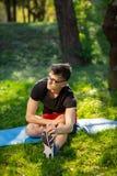 Ung man i exponeringsglas som utomhus utbildar yoga Den sportiga grabben gör koppla av övning på en blå yoga mattt, parkerar in k royaltyfria bilder