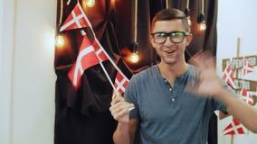 Ung man i exponeringsglas som vinkar en dansk flagga, le som ser in i kameran stock video