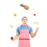 Ung man i förkläde som jonglerar med frukter Arkivfoto