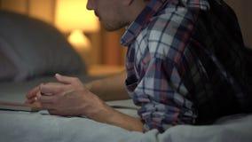 Ung man i förtvivlan som ligger på säng som ser fotoet med flickvännen, sorgsenhet arkivfilmer