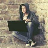 Ung man i grön hoodie genom att använda bärbara datorn på momenten Arkivbild