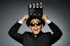 Ung man i hållande clapperboard för elegant dräkt arkivfoto