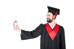 Ung man i hållande diplom för avläggande av examenkappa Royaltyfria Bilder