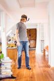 Ung man i hans lägenhet, genom att använda Vr exponeringsglas Arkivfoto