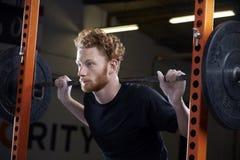 Ung man i idrottshalllyftande vikter på skivstång Royaltyfri Foto