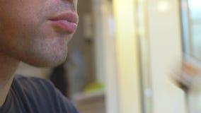 Ung man i kafé som äter sushi med pinnar 4k närbild lager videofilmer