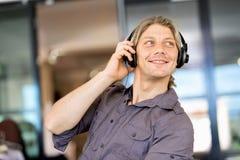 Ung man i kontoret med hörlurar Arkivbilder