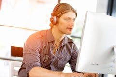 Ung man i kontoret med hörlurar Fotografering för Bildbyråer