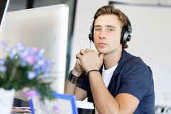 Ung man i kontoret med hörlurar Arkivbild