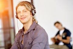 Ung man i kontoret med hörlurar Royaltyfria Foton