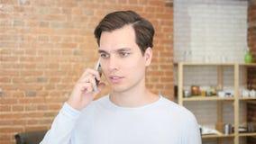 ung man i kontoret på telefonen med hörlurar med mikrofon, video pratstund royaltyfria bilder