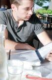 Ung man i läs- meny för restaurang arkivbilder