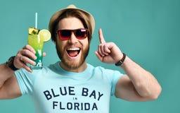 Ung man i lyckliga jubel för hatt som och för röd fruktsaft för drink för coctail för solglasögonhållmargarita pekar fingret upp  royaltyfria bilder