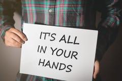 Ung man i plädskjortan som rymmer ett plakat med text: DET är ALLA IN DINA HÄNDER! fotografering för bildbyråer