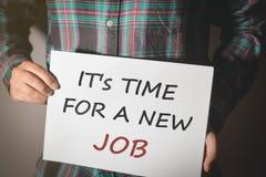 Ung man i plädskjortan som rymmer ett plakat med text: TIME FÖR ETT NYTT JOBB! royaltyfri fotografi