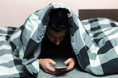 Ung man i pyjamas genom att använda en mobiltelefon royaltyfri foto