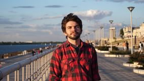 Ung man i röd skjorta som går ner stranden lager videofilmer