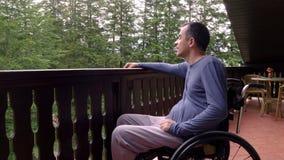 Ung man i rullstol som kopplar av på terrass arkivfilmer