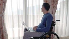 Ung man i rullstolarbete på bärbar datordatoren hemma arkivfilmer
