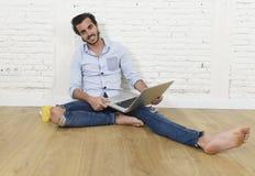 Ung man i sammanträde för blick för tillfällig stil för hipster modernt på vardagsrumhemgolvet som arbetar på bärbara datorn Royaltyfri Fotografi