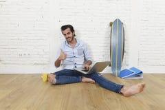 Ung man i sammanträde för blick för tillfällig stil för hipster modernt på vardagsrumhemgolvet som arbetar på bärbara datorn Royaltyfri Bild