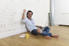 Ung man i sammanträde för blick för tillfällig stil för hipster modernt på vardagsrumhemgolvet som arbetar på bärbara datorn Arkivbild