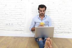 Ung man i sammanträde för blick för tillfällig stil för hipster modernt på vardagsrumhemgolvet som arbetar på bärbara datorn Fotografering för Bildbyråer