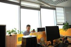 Ung man i smart telefon för smart innehav för tillfälliga kläder och se den, medan sitta på hans arbetsplats i regeringsställning Royaltyfria Foton