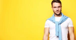 Ung man i smarta tillfälliga kläder som ser kameran över gulingbac fotografering för bildbyråer
