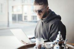 Ung man i solexponeringsglas som rymmer bärbara datorn på hans knä och arbete på det i kafé royaltyfri bild