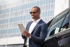 Ung man i solglasögon som lutar på bilen som bläddrar digitalt le för minnestavla som är gladlynt royaltyfri foto