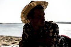 Ung man i sommarhatten som ligger på havsstranden ett slut upp stående arkivbilder