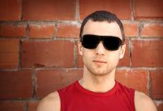 Ung man i svart solglasögon över den gammala tegelstenväggen Arkivbild
