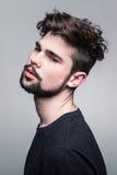 Ung man i svart T-tröja med den trendiga frisyren royaltyfri fotografi