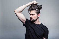 Ung man i svart T-tröja med den trendiga frisyren royaltyfri foto