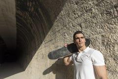 Ung man i tunnel med att posera för skateboard arkivfoto