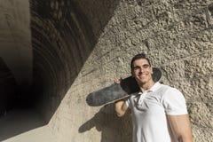 Ung man i tunnel med att posera för skateboard royaltyfria bilder