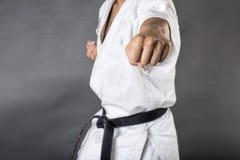 Ung man i utbildningskampsport för vit kimono och för svart bälte Fotografering för Bildbyråer