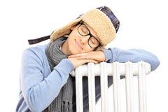 Ung man i vinterhatt som sover på ett element royaltyfri bild