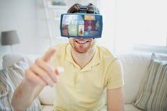 Ung man i virtuell verklighethörlurar med mikrofon eller exponeringsglas 3d Arkivbilder