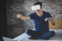 Ung man i virtuell verklighethörlurar med mikrofon eller exponeringsglas som 3d spelar videoen Royaltyfri Bild