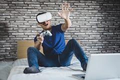Ung man i virtuell verklighethörlurar med mikrofon eller exponeringsglas som 3d spelar videoen Arkivfoto