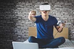 Ung man i virtuell verklighethörlurar med mikrofon eller exponeringsglas som 3d spelar videoen Arkivfoton